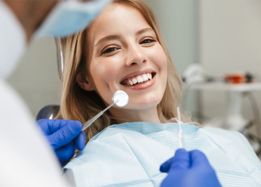 The woman is happy to visit her dentist.